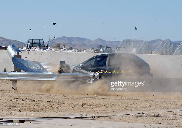 A compact coupe hits the end of a guardrail head on during a crash test at Karco Engineering LLC safety testing facility in Adelanto California US on...