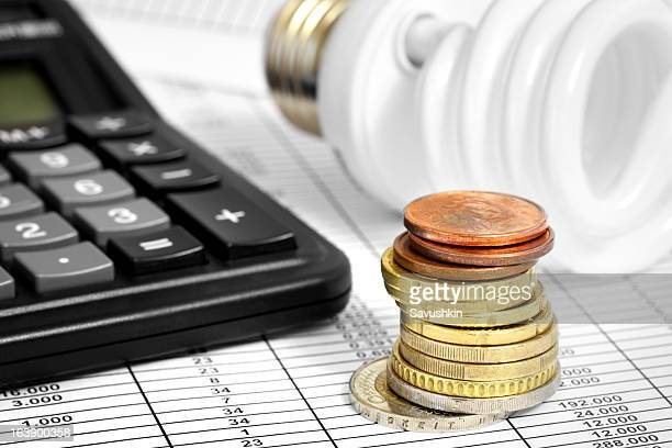 Bombilla fluorescente compacta y moneda, calculadora pila
