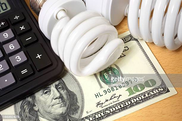 compact fluorescent lightbulbs, calculator and hundred dollar bill - energy efficient stock photos and pictures