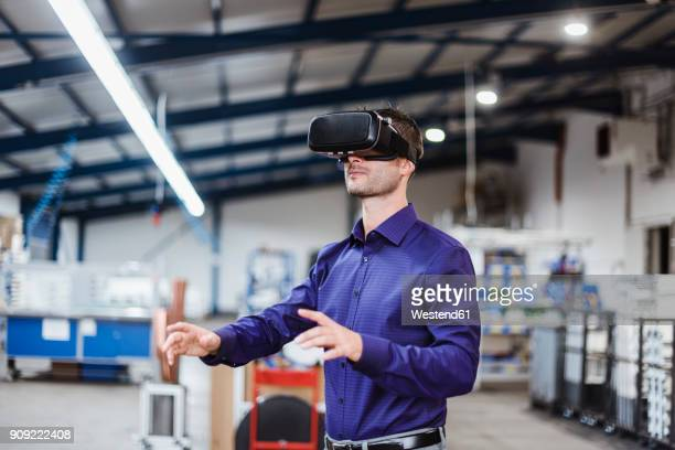 company employee wearing vr goggles in shop floor - erweiterte realität stock-fotos und bilder