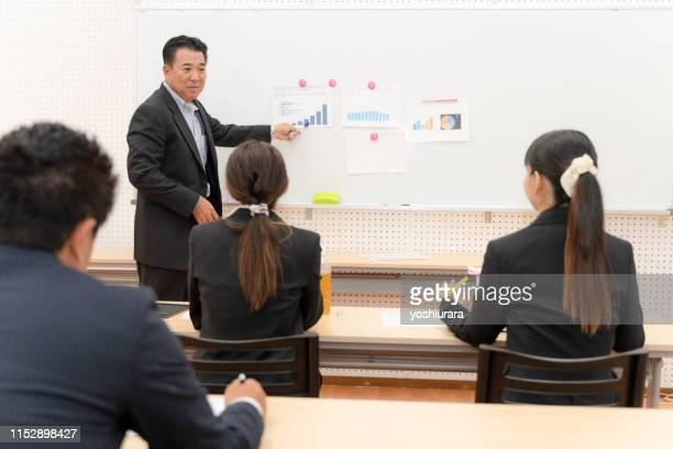 先輩からトレーニングを受ける会社員 - showing ストックフォトと画像
