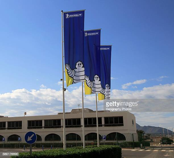 Company flags with logo Bibendum figure flying outside Michelin factory and research establishment Almeria Spain