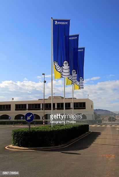 Company flags with logo Bibendum figure flying outside Michelin factory and research establishment Almeria Spain