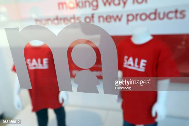 A company logo sits displayed on a Mothercare Plc store widow in front of mannequins wearing 'sale' tshirts inside a Mothercare baby and children's...