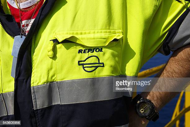 A company logo sits on the overalls of an oil worker on the Casablanca oil platform operated by Repsol SA in the Mediterranean Sea off the coast of...