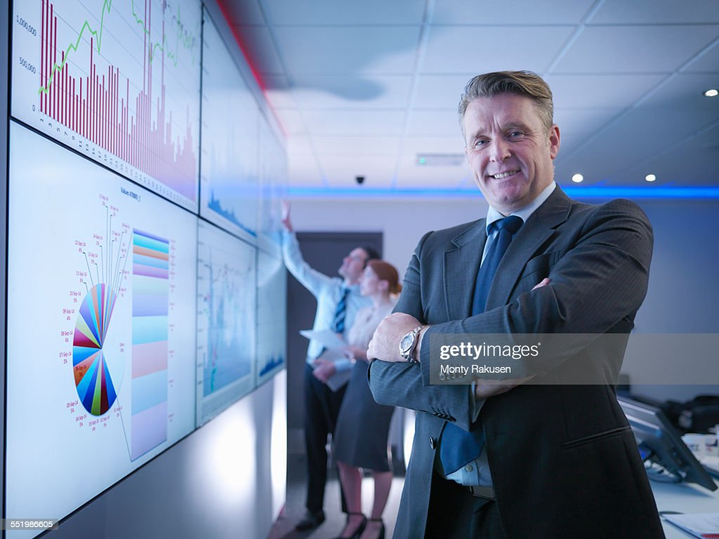 Company manager in front of graphs on screen in meeting room, portrait : Stock Photo