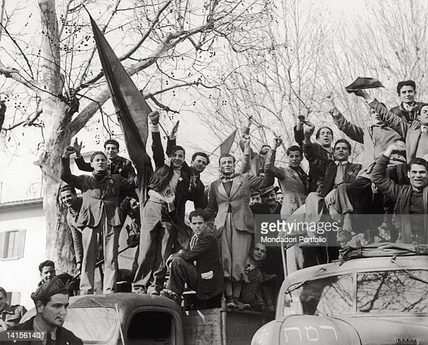 A company of communist partisans on two motor vehicles greets before leaving to join the allied troops in Emilia Romagna Italy February 1945