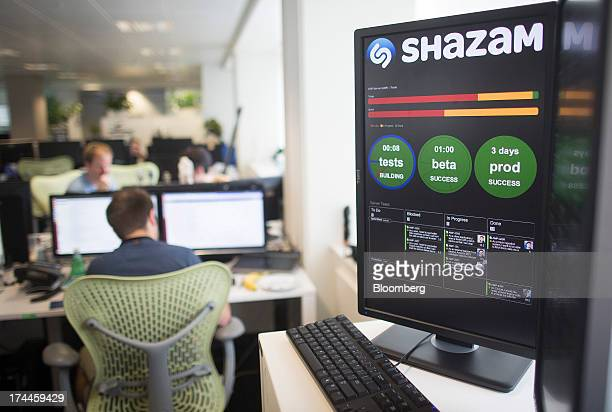 Company performance data is displayed on a monitor as employees work at the Shazam Entertainment Ltd headquarters in London UK on Friday July 26 2013...
