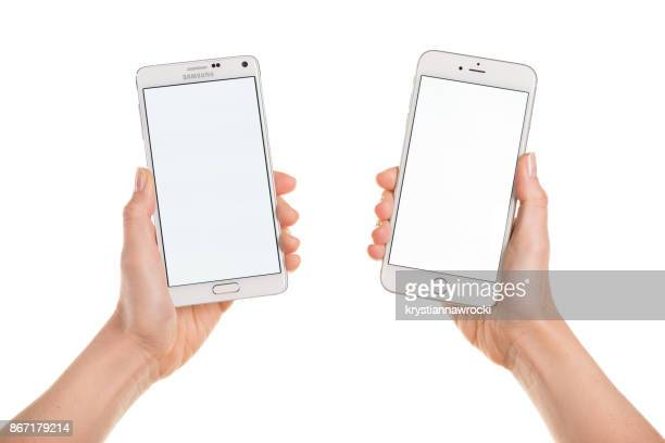 comparing iphone 6 plus and samsung galaxy note 4 displaying white - two objects stock photos and pictures