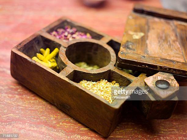 Compartmented wooden box with various spices, close-up