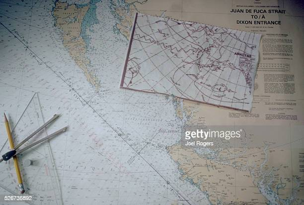 A compass and a protractor lay on a map of the Inside Passage from Washington to Alaska