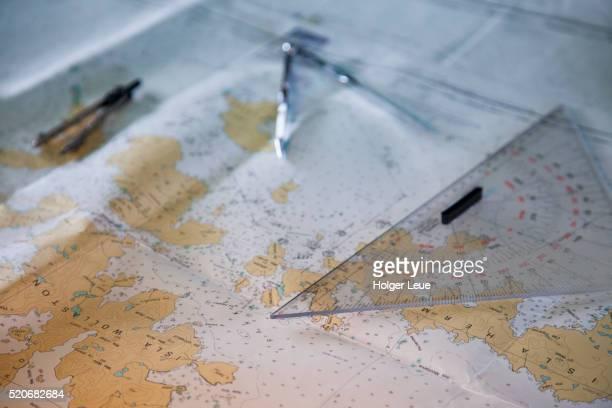 Compass and protractor on sea chart aboard cruise ship MS Deutschland (Reederei Peter Deilmann)
