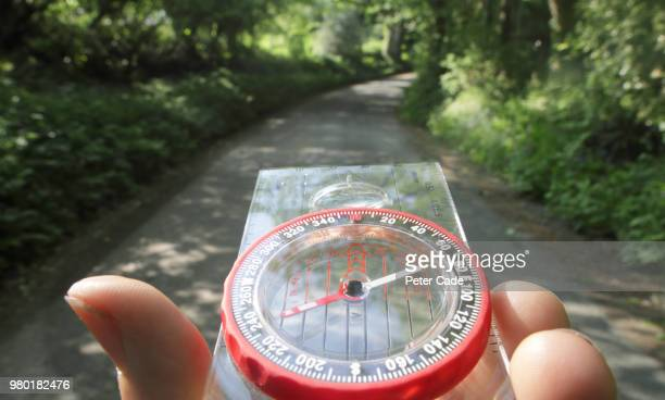 compass being used on country lane - guidance stock pictures, royalty-free photos & images