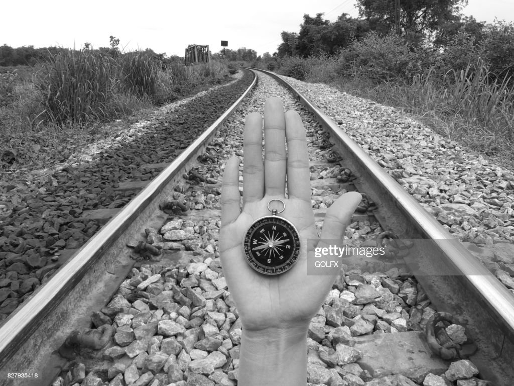 Compass in hand against railroad black and white tone stock photo