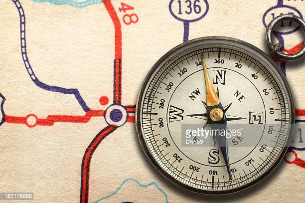 Compass sitting on top of road map showing highway junction