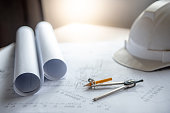 Compass tool and safety helmet on architectural drawing plan of house project, blueprint rolls on working table, Architecture and building construction industry concepts