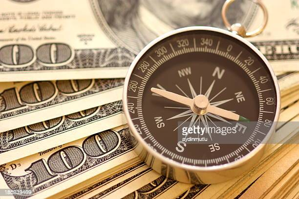 compass used as paperweight on top of 100 dollar bills - west direction stock pictures, royalty-free photos & images