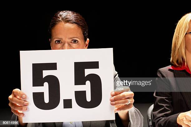competition judge holding up 5.5 scorecard - judge sports official stock pictures, royalty-free photos & images