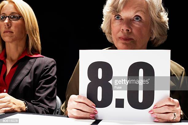 competition judge holding up 8.0 scorecard - judge sports official stock pictures, royalty-free photos & images