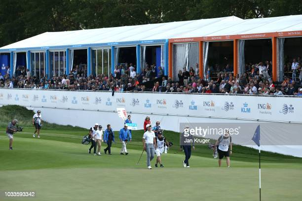 A competition winner walks down the 14th hole with players after competing for a 'nearest to the pin' with the pro's during day three of the KLM Open...