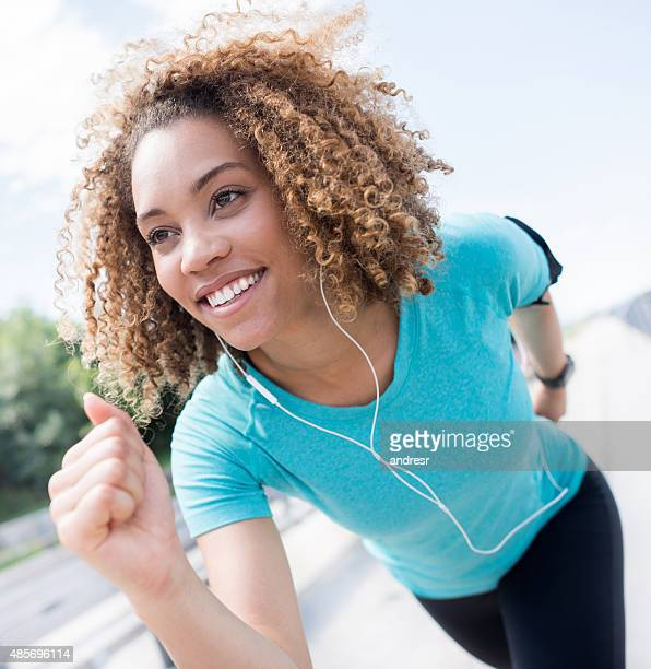 Competitive black woman running outdoors