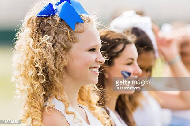 competitive cheerleading squad cheering at football game - cheerleaders stock photos and pictures