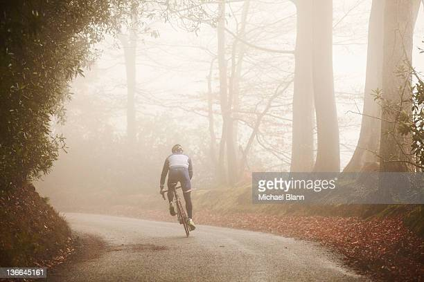 competitive cyclist riding along foggy road - forward atlet bildbanksfoton och bilder