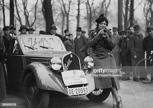 A competitor applying lipstick before the start of the Paris Vichy SaintRaphaël women's rally in the Place de la Concorde Paris 1936 Her car is a...