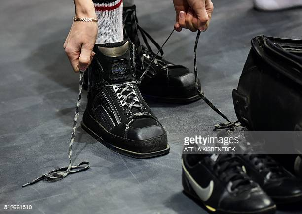 A competitor changes her shoes for special shooting shoes in AUDI Arena of Gyor on February 26 2016 during the qualification round of 10m air rifle...