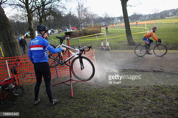 A competitor cleans his bike before the 'Veteran Men 50' category race at the 2013 National CycloCross Championships in Peel Park on January 12 2013...