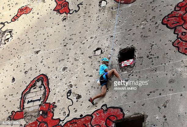 TOPSHOT A competitor climbs the holeridden facade of Beirut's alKamal building which was severely damaged during the Lebanese civil war during an...