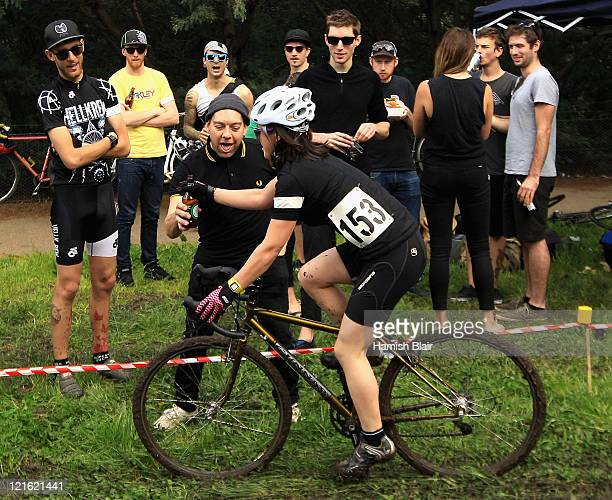A competitor collects a beer from a rowdy spectator during the Dirty Deeds Urban Cyclocross at Harrison St Velodrome on August 21 2011 in Melbourne...