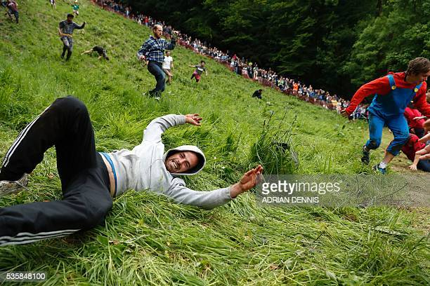 A competitor comes tumbling down the hill in pursuit of a round Double Gloucester cheese during the annual Cooper's Hill cheese rolling competition...