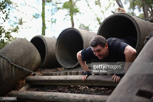 A competitor crawls through a concrete pipe in the Plumber's Crack obstacle as he competes in the Tough Bloke Challenge at the Cataract Scout Park on...