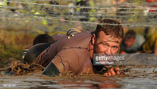 A competitor crawls under barbed wire during the Tough Guy Challenge endurance race on January 27 2013 in Telford England Every year thousands of...