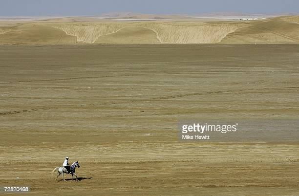 A competitor crosses the desert during the Equestrian Endurance Event at the Mesaieed Endurance Course 15th Asian Games Doha 2006 on December 14 2006...
