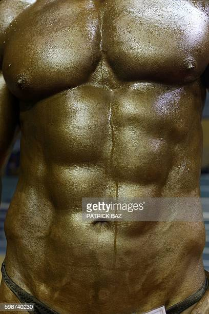 A competitor displays his sixpack abs on stage during Lebanon's bodybuilding championship on August 27 2016 in the capital Beirut / AFP / PATRICK BAZ
