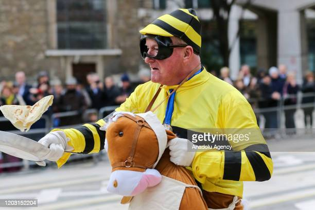 A competitor dressed as a bubble bee flips a pancake during the annual InterLivery Pancake Race on Shrove Tuesday at The Guildhall in London United...
