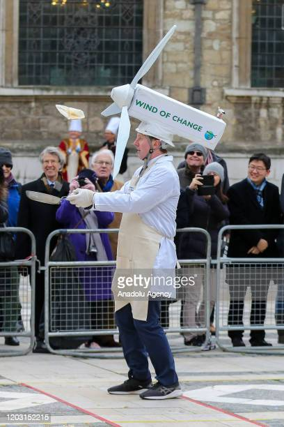 A competitor dressed as fan flips a pancake during the annual InterLivery Pancake Race on Shrove Tuesday at The Guildhall in London United Kingdom on...