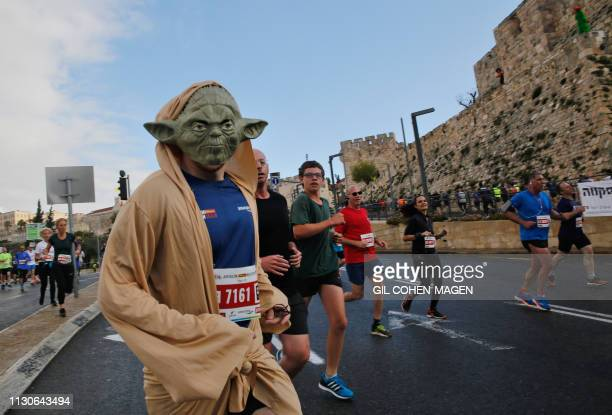 Competitor dressed as Star Wars' last Jedi Yoda runs along the Old City ramparts during Jerusalem's 9th International Marathon, on March 15, 2019.