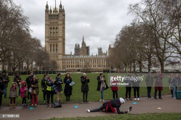 A competitor falls on the first lap during the annual Parliamentary Pancake Race in Victoria Tower Gardens on Shrove Tuesday on February 13 2018 in...