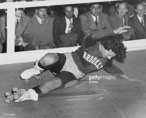 A competitor from the Brooklyn team takes a fall during a roller derby at the 69th Regiment Armory New York City circa 1949