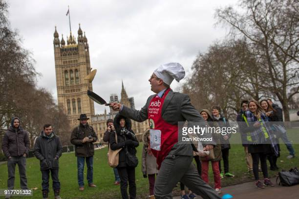 A competitor from the journalist team runs a lap during the annual Parliamentary Pancake Race in Victoria Tower Gardens on Shrove Tuesday on February...