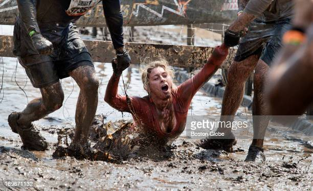 A competitor gets dragged out after completing the Electric Eel where dangling wires give off electronic shocks during a Tough Mudder event held at...