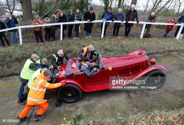A competitor has her car pushed up the 'Test Hill' as they take part in the Vintage SportsCar Club annual driving test day at Brooklands Museum in...