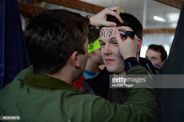 A competitor has his ID number drawn onto his head in permanent marker before the annual Tough Guy Challenge race on February 1 2015 in Telford...