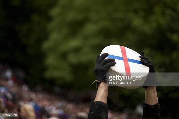 A competitor holds a round Double Gloucester cheese aloft after winning a cheese rolling race on Coopers Hill on May 25 2009 during the annual cheese...