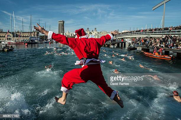 A competitor in Christmas fancy dress jumps into the sea during the 105th Barcelona Traditional Christmas Swimming Cup at the Old Harbour of...