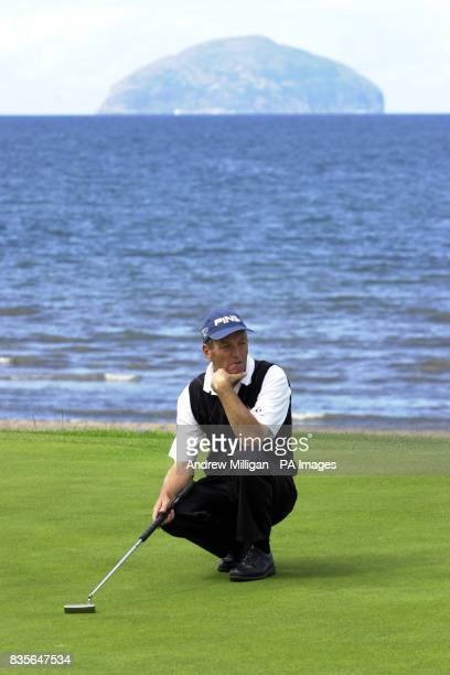 Competitor in front of the Ailsa Craig rock at the Senior British Open Championship Turnberry