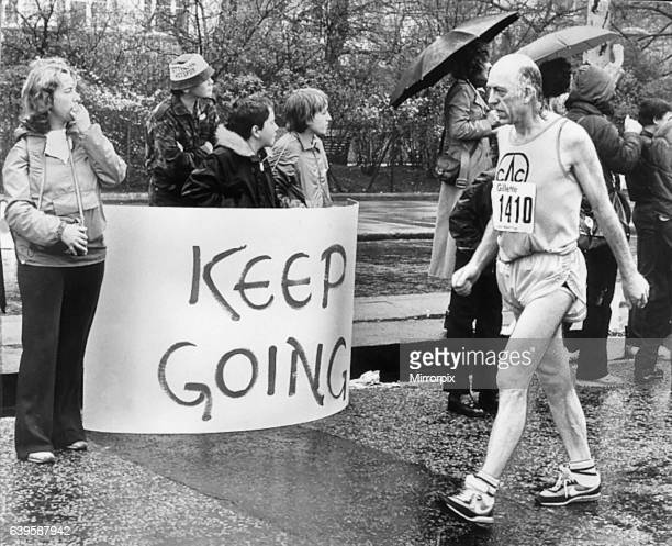 A competitor in the first ever London Marathon March 1981 George Douthwaite at walking pace passing a sign saying Keep Going